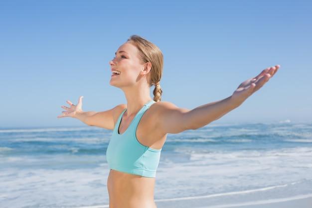 Dysponowana kobiety pozycja na plaży z rękami out