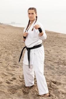 Dysponowana młoda dziewczyna w karate kostiumu plenerowym