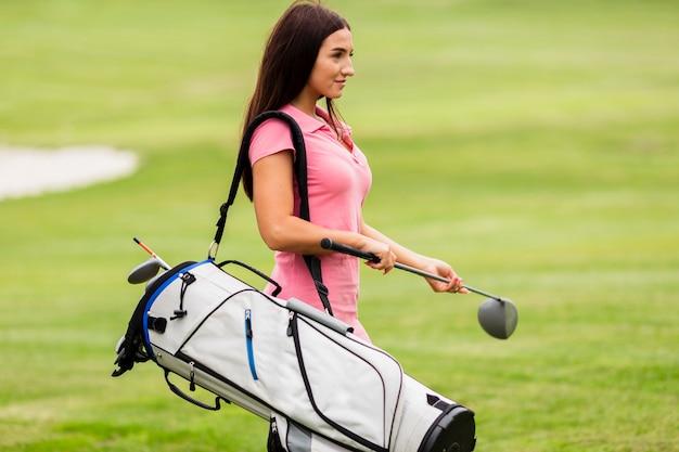 Dysponowana młoda kobieta niesie kije golfowych