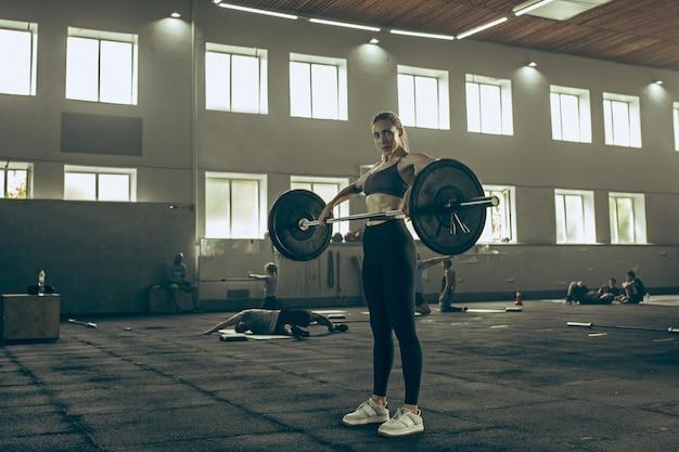 Dysponowana młoda kobieta podnosi sztangę pracującą w gym out