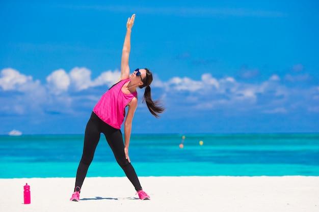 Dysponowana młoda kobieta robi ćwiczeniom na tropikalnej biel plaży w jej sportswear