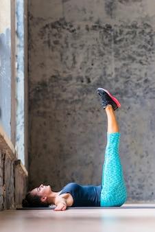 Dysponowana młoda kobieta robi rozciągania ćwiczeniu na joga macie