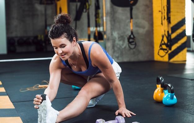 Dysponowana młoda kobieta rozciąga jej nogę w sprawność fizyczna klubie