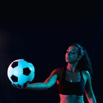 Dysponowana młoda kobieta trzyma piłki nożnej piłkę