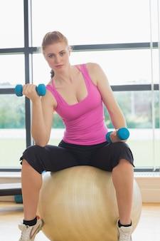 Dysponowana piękna kobieta siedzi na ćwiczenie piłce z dumbbells
