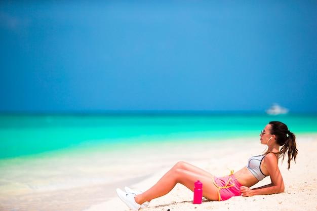 Dysponowana sport młoda kobieta na tropikalnej biel plaży