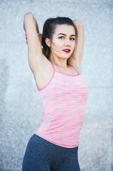 Dysponowana sprawności fizycznej kobieta robi rozciąganiu ćwiczy outdoors