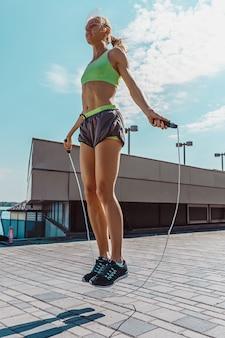 Dysponowana sprawności fizycznej kobieta robi sprawności fizycznej ćwiczy outdoors