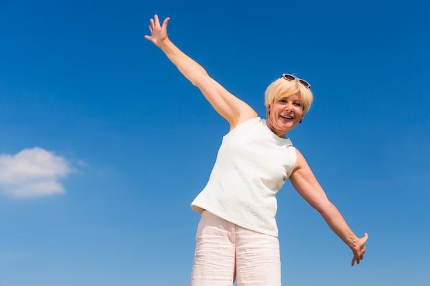 Dysponowana starsza kobieta patrzeje do nieba podczas gdy cieszący emerytura