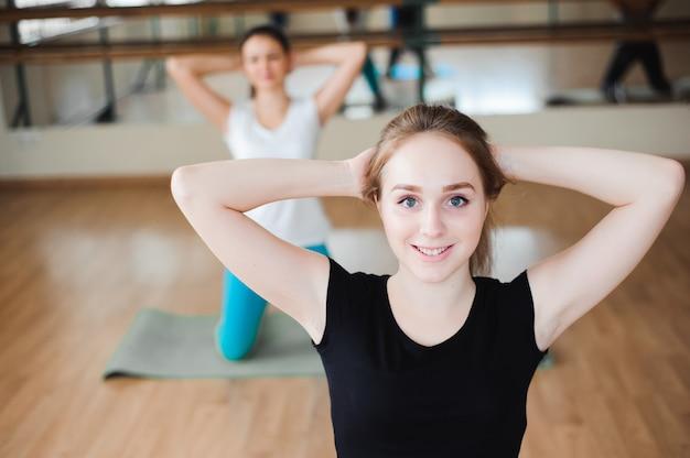 Dysponowana uśmiechnięta grupa robi ćwiczeniu w gym