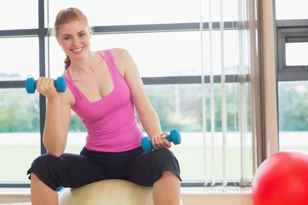 Dysponowana uśmiechnięta kobieta siedzi na ćwiczenie piłce z dumbbells