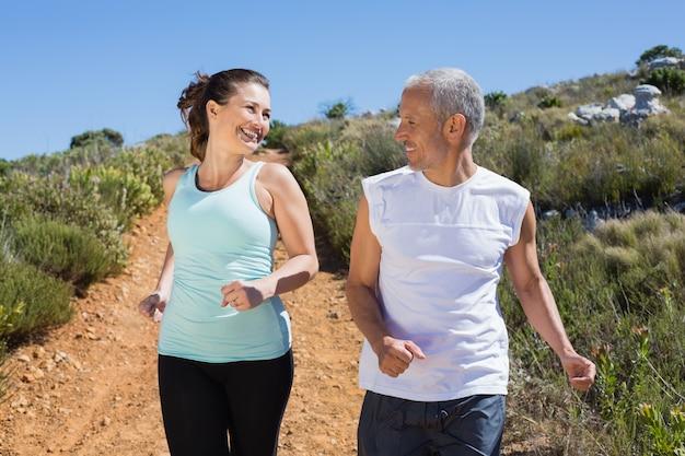 Dysponowana uśmiechnięta para jogging w dół halnego ślad