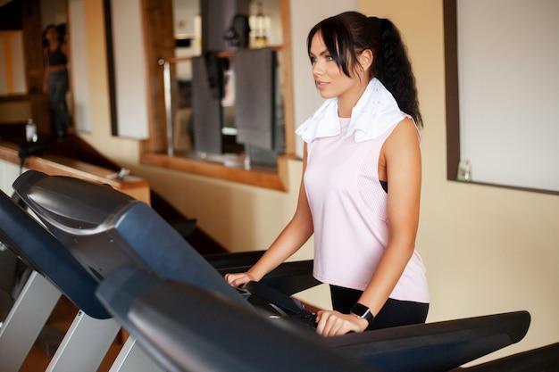 Dysponowane kobiety biega na bieżniach robi cardio szkoleniu w gym, zdrowy stylu życia pojęcie