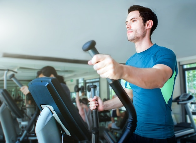 Dysponowany caucasian mężczyzna biegający na wyposażenie salowym gym