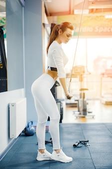 Dysponowany kobieta treningu triceps podnosi ciężary w gym