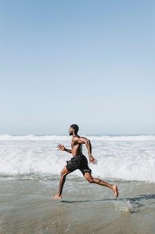 Dysponowany mężczyzna bieg przy plażą