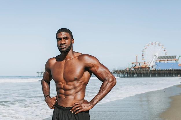 Dysponowany mężczyzna pozuje przy plażą