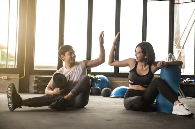 Dysponowany młody człowiek i kobieta ćwiczy w gym