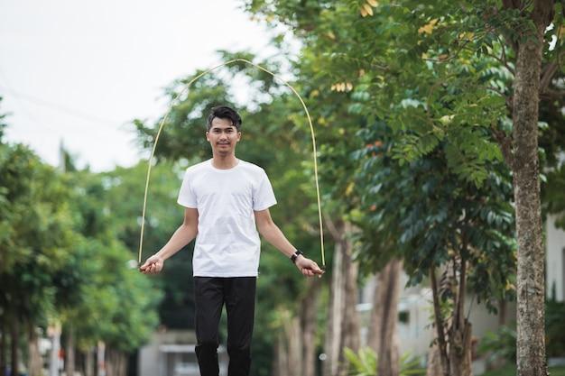 Dysponowany młody człowiek z skok arkaną w parku