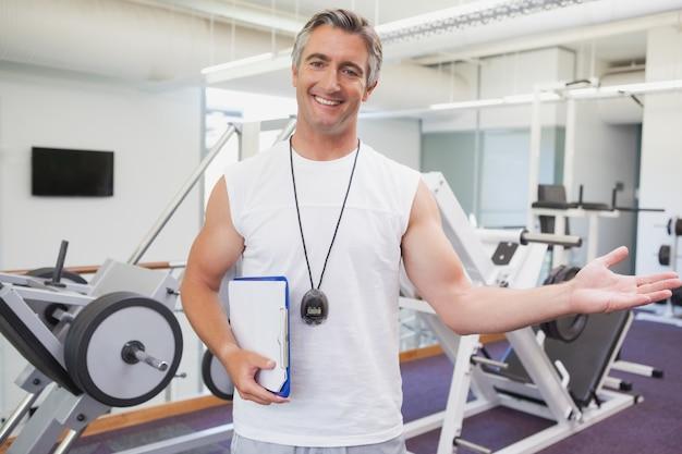 Dysponowany osobisty trener ono uśmiecha się przy kamerą w sprawności fizycznej studiu przy gym