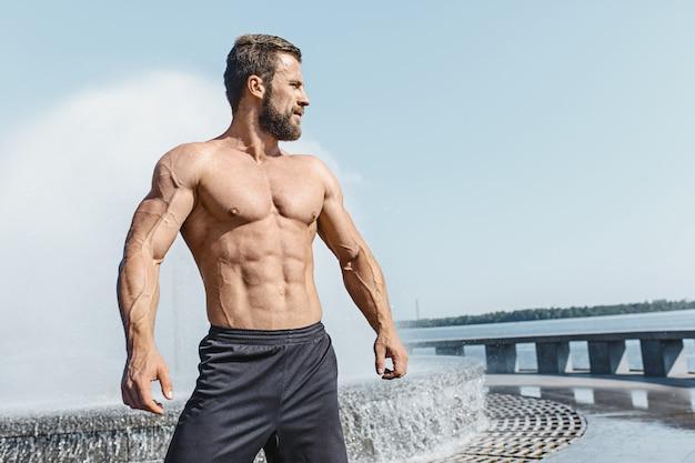 Dysponowany sprawność fizyczna mężczyzna pozuje przy miastem