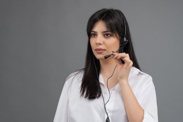Dyspozytor z zestawem słuchawkowym odpowiadającym na pytania klientów w izolowanym centrum telefonicznym