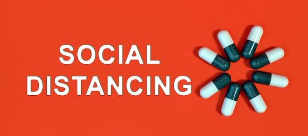 Dystans społeczny - biały tekst na czerwonym tle z kapsułkami pigułki
