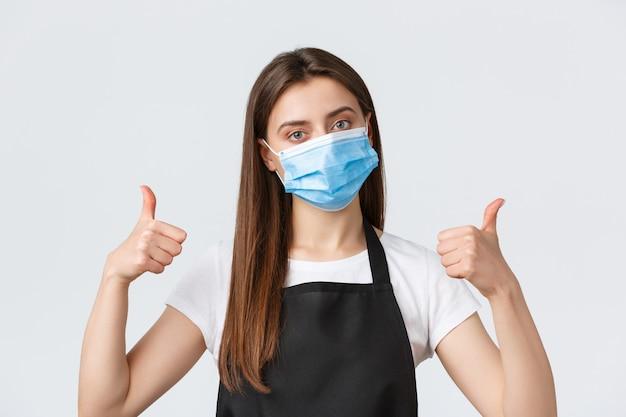 Dystans społeczny covid-19, pracownicy kawiarni, kawiarnie i koncepcja koronawirusa. zbliżenie na zdeterminowaną ładną baristkę, kelnerkę w masce medycznej, pokazuje uniesione kciuki, zapewnia bezpieczną obsługę klienta