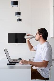 Dystans społeczny. e-learning i nauczanie. młody uśmiechnięty mężczyzna w białej koszuli przy laptopie pracującym w domu, pijący wodę z termosu
