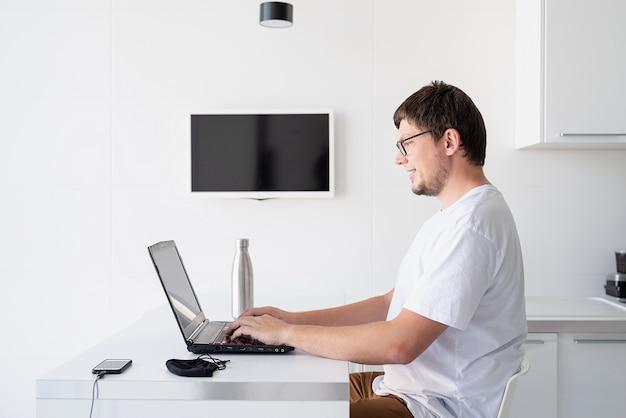Dystans społeczny. e-learning i nauczanie. młody uśmiechnięty mężczyzna w białej koszuli przy laptopie pracującym w domu