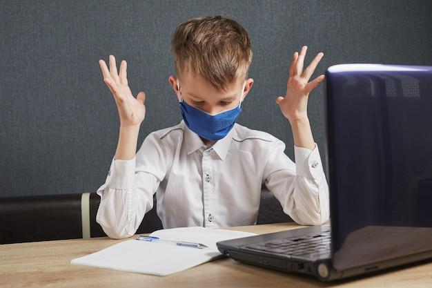 Dystans społeczny, izolacja, koncepcja edukacji online. chłopiec studiuje pracę domową matematykę podczas lekcji online w domu.