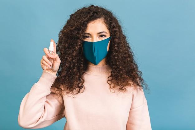 Dystans społeczny, koncepcja zapobiegania pandemii covid-19. kobieta w masce medycznej trzyma środek dezynfekujący do rąk, myje ręce podczas koronawirusa.