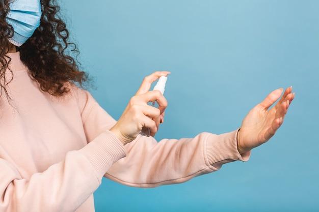 Dystans społeczny, koncepcja zapobiegania pandemii covid-19. kobieta w masce medycznej trzymając środek dezynfekujący do rąk