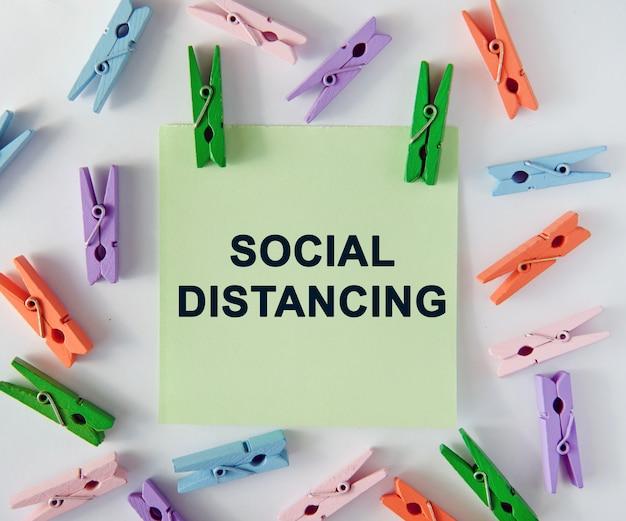 Dystans społeczny - tekst na kartce notatek i kolorowe spinacze do bielizny