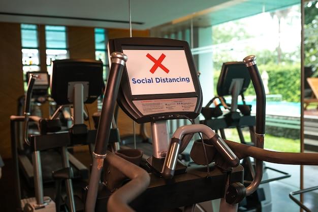 Dystans społeczny w nowej normalnej koncepcji, ludzie mężczyźni i kobiety ćwiczący w siłowni fitness