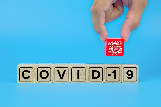 Dystans społeczny z ikonami tekstowymi covid-19 na drewnianym bloku zabawek.