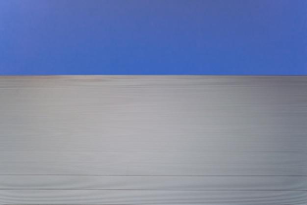 Dystopian niebieskie niebo ściana z zatłoczonymi poziomymi metalowymi liniami.