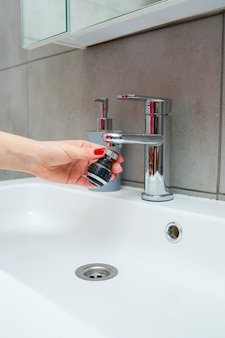 Dysza obrotowa na mikserze do regulacji przepływu wody. biała umywalka łazienkowa do mycia rąk