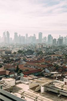 Dżakarta cityscape z wysokim wzrostem, wieżowce i czerwone dachówki dachowe lokalnych budynków