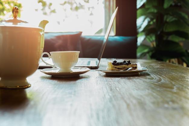 Dzbanek do herbaty z kubkiem i jagodowym sernikiem na drewnianym stole.