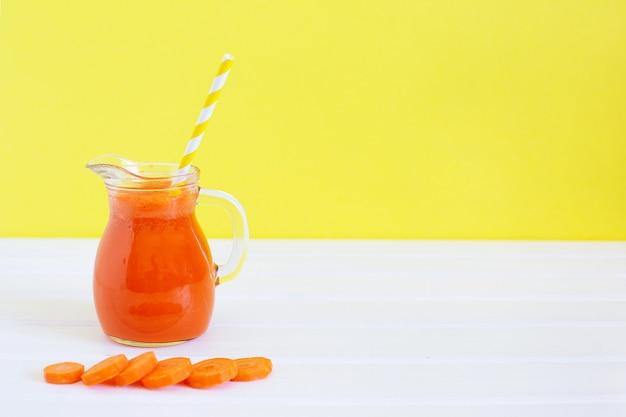 Dzbanek ekologicznego soku z marchwi i świeżej marchwi na kolorowym tle. zdrowe odżywianie się, dieta zasadowa. letnia koncepcja żywności.