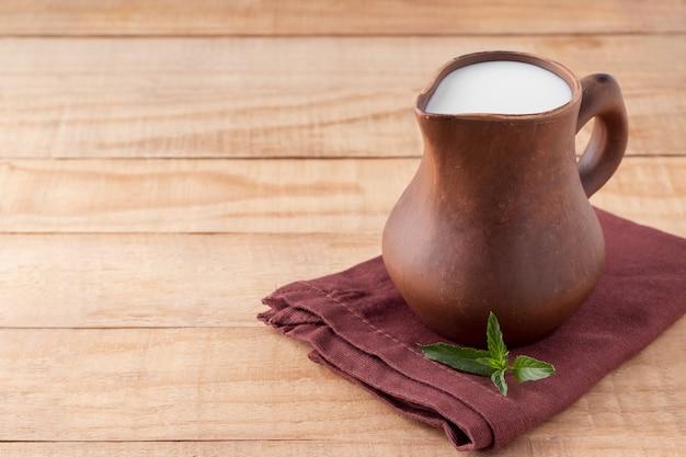 Dzbanek jogurtu kefirowego lub ajranu na drewnianym stole miejsce na tekst domowy fermentowany produkt mleczny