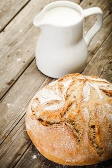 Dzbanek mleka, białego chleba na drewnianym stole