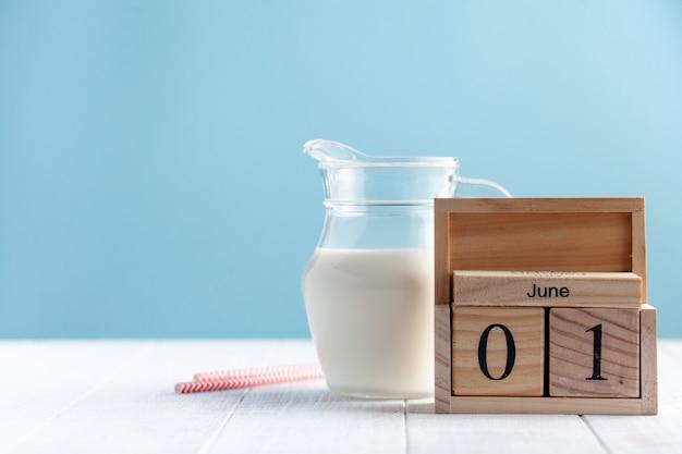 Dzbanek mleka i drewniany kalendarz 1 czerwca na niebieskim tle. dzień mleka napis. skopiuj miejsce.