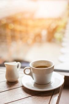 Dzbanek mleka i filiżanki kawy na drewnianym stole w pobliżu szklanego okna