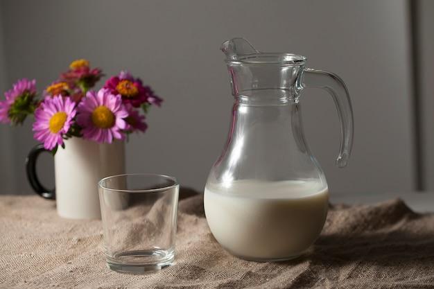 Dzbanek mleka i szklanka w stylu rustykalnym na jutowym obrusie