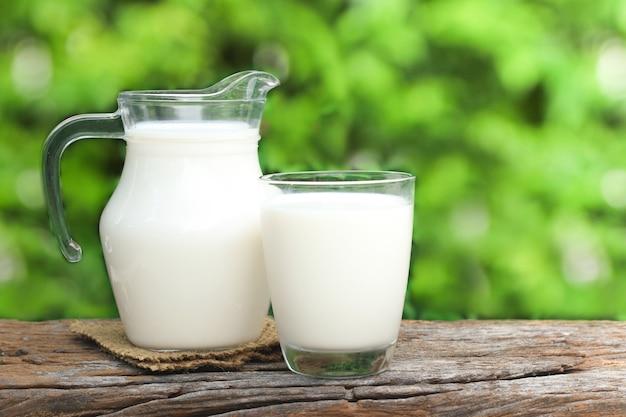 Dzbanek mleka i szklankę mleka na drewnianym stole.