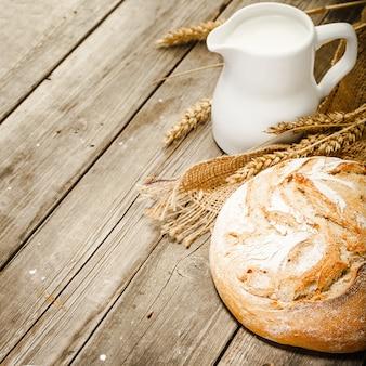 Dzbanek na mleko, biały chleb, żyto i worek na drewnianym stole