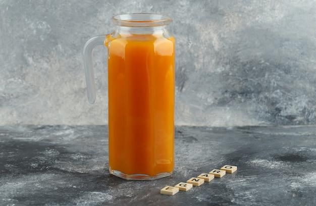 Dzbanek soku pomarańczowego z drewnianymi literami na marmurowym stole.