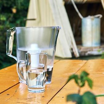 Dzbanek z filtrem i przezroczysta filiżanka wody na tle studni wioski